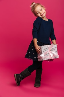 Full length image of pleased young girl holding gift box