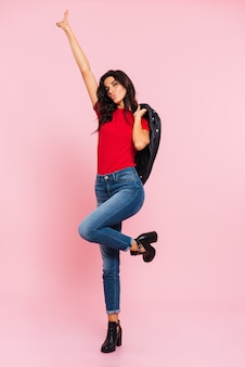 Full length image of pretty brunette woman posing in studio and showing peace sign while looking at the camera over pink