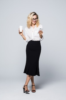 Full length image of pretty business woman in formal wear standing and using cell phone with takeaway coffee in hand isolated over gray wall