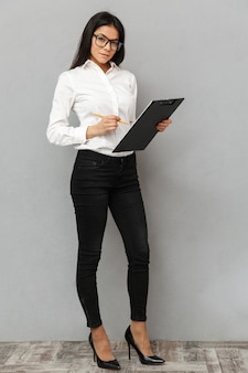 Full length image of pretty woman wearing businesslike outfit and glasses holding clipboard with papers and writing down notes in documents, isolated over gray background
