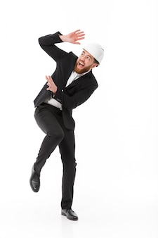 Full length image of scared business man in protective helmet