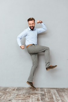 Full length image of screaming bearded man in business clothes