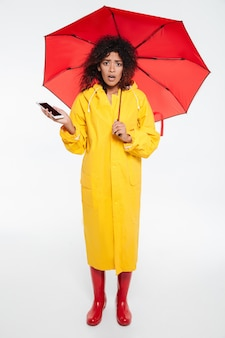 Full length image of shocked african woman in raincoat hiding under umbrella while holding smartphone and looking at the camera