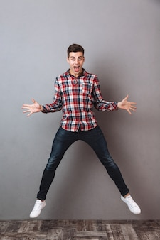 Full length image of shocked screaming man in shirt and jeans jumping and looking