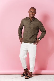 Full length image of smiling african man holding arms on hips and looking