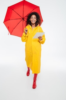 Full length image of smiling african woman in raincoat