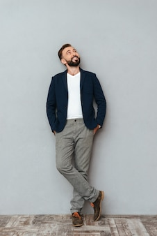Full length image of smiling bearded man in busines clothes holding arms in pockets and looking up over gray
