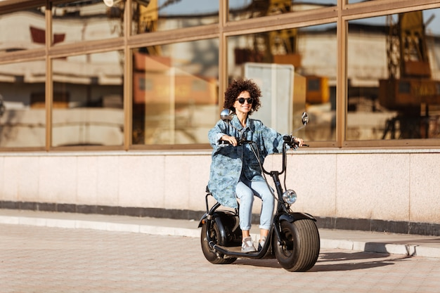 Full length image of smiling curly woman in sunglasses rides on modern motorbike outdoors