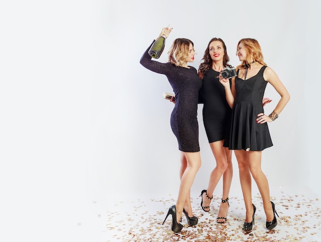 Full length image of three happy girls spending time at crazy party, dancing, having fun and laughing. wearing elegant casual dress, heels, bright make up. drinking champagne.  space for text.