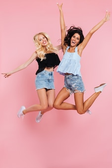 Full length image of two happy friends jumping in studio