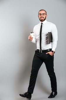 Full-length image of young unshaved man in glasses and suit walking with to-go coffee and laptop in hands, isolated over gray wall