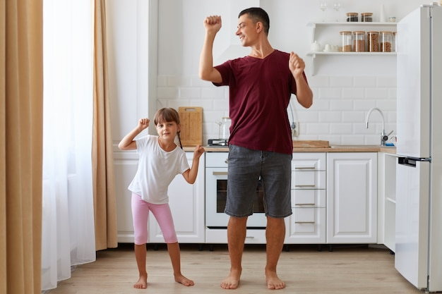 Full length indoor shot of happy family father and dark haired daughter with pigtails dancing in kitchen together, spending time and having fun at home.