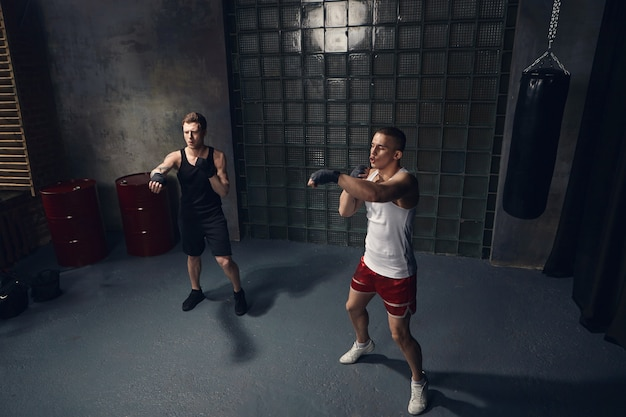 Full length isolated portrait of two handsome caucasian guys exercising indoors together wearing stylish sports clothes and boxing bandages, reaching out hands while mastering punches in modern gym