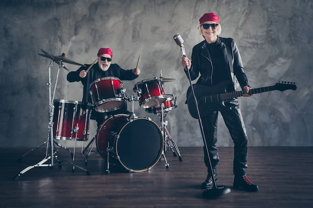 Full length of lady man rock group perform play drum instruments sing song