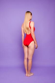 Full length of lady turned back wearing bright swim wear