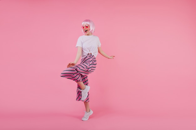 Милая девушка в полный рост танцует в белых кроссовках. крытый портрет довольной кавказской дамы в розовых перьюк и модных брюках