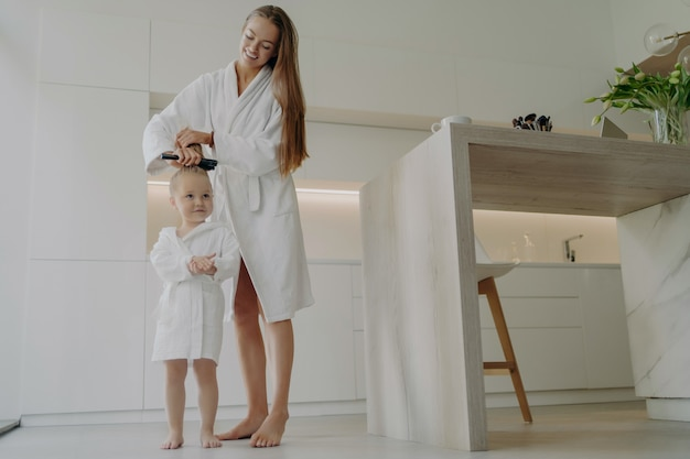 Full length of loving mother in white bathrobe brushing hair of cute little daughter after taking shower or bath while standing in modern kitchen at home, mom teaching small child good hygiene habits