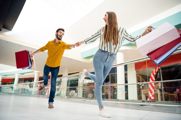 Full length low angle view photo of cheerful pretty lady lead handsome guy hurry next store wanna buy one more shirt dress shoes carry many bags shopping center wear casual outfit indoors