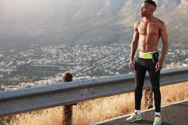 Full length male runner with muscular body, has marathone training, thoughtful expression, admires beautiful panoramic mountain view, thinks about goal challenge, enjoys outdoor cardio workout
