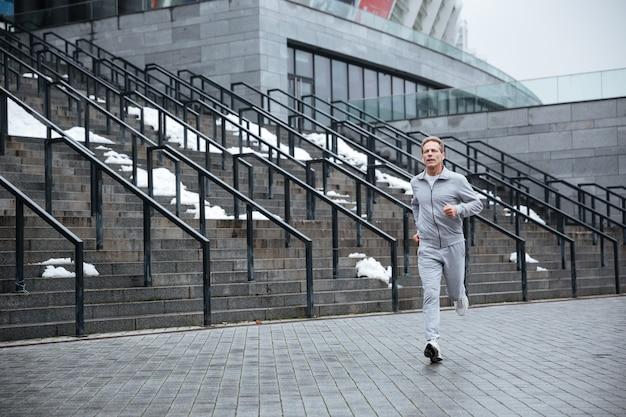 전체 길이 계단 근처 실행 회색 운동복에 남자.