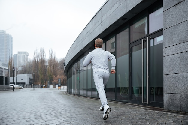 거리에서 실행되는 회색 운동복에 전체 길이 남자. 뒷면보기