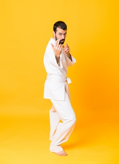 Full length  of mandoing karate over isolated yellow wall