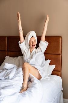 Ritratto mattutino a figura intera di una bella donna appena alzata in un hotel di lusso, rilassarsi e divertirsi sul letto.