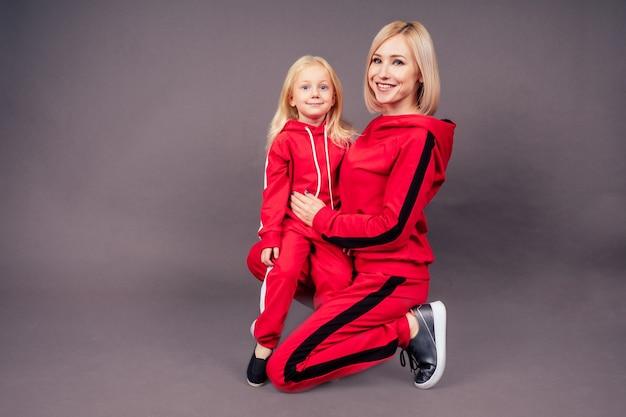 스포츠 정장을 입은 딸과 함께 온전한 어머니. 빨간 세련된 정장 스튜디오 검정색 배경, 활동적인 스포츠 가족 힙합 댄서에서 바닥에 앉아 있는 어린 소녀와 함께 아름다운 젊은 금발 여성.