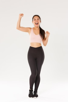 Full length of motivated and excited female athelte, asian fitness girl in activewear fist pump and shouting encouraged, gaining workout goal, satisfied with productive good training in gym.