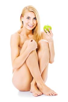 白い背景の上に孤立して座っている間リンゴを保持している完全な長さの裸の女性