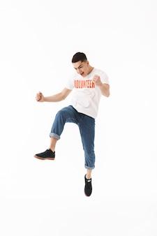 В полный рост счастливый молодой человек в футболке-добровольце прыгает изолированно над белой стеной, празднуя успех
