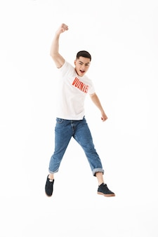 Full length od a happy young man wearing volunteer t-shirt jumping isolated over white wall, celebrating success