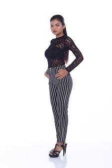 Полная длина 20-х годов азиатская женщина в модном черном платье с длинными рукавами и брюками. девушка с загорелой кожей стоит и выражает эмоции, чувствуя сильные позы на белом фоне изолированы
