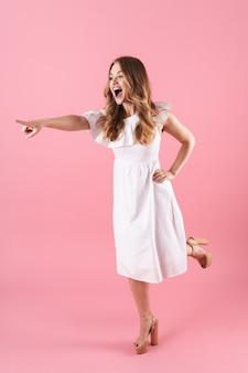 ピンクの壁の上に孤立して立っている夏のドレスを着て、離れて指している美しい陽気な若いブロンドの女の子の全長