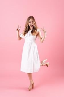 ピンクの壁の上に孤立して立って、ポーズをとって夏のドレスを着て美しい陽気な若いブロンドの女の子の全長