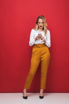 携帯電話を持って、赤い背景の上に孤立して立っている美しい物思いにふける若いブロンドの女性の全長