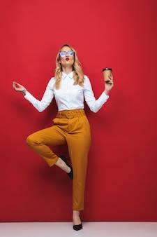 Полная длина красивой молодой блондинки, стоящей изолированно на красном фоне, балансируя, держа чашку кофе