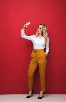 Полная длина красивой молодой блондинки, стоящей изолированно на красном фоне, принимая селфи