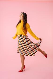 ピンクの上に分離されたカラフルな服を着て、ジャンプする美しい若い女性の全長