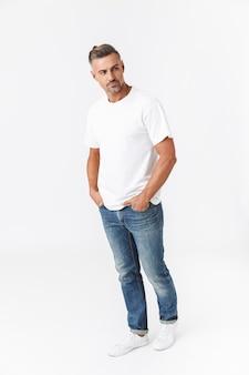 Полная длина случайного красавца в футболке, стоящего изолированно на белом, позирует