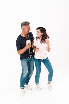 白い壁の上に孤立して立っているカジュアルな服を着て、イヤホンで音楽を聴きながら踊る陽気な魅力的なカップルの全長