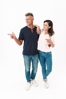 白い壁の上に孤立して立っているカジュアルな服を着て、離れて指している陽気な魅力的なカップルの全長