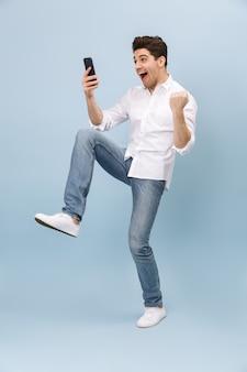 青で孤立して立っている、携帯電話を持って、祝う陽気なハンサムな若い男の全長