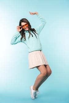 Полная длина веселая молодая брюнетка женщина прыгает через синий backgorund, позирует