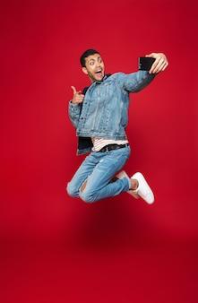 Веселый молодой человек в теплой джинсовой куртке в полный рост прыгает через красную стену и делает селфи