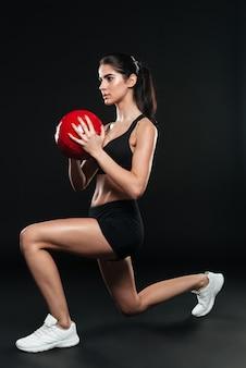 Концентрированная спортивная женщина в полный рост делает приседания и держит весовой мяч над черной стеной