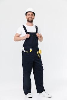 Уверенный в себе бородатый мужчина-строитель в полный рост в комбинезоне и каске стоит изолированно над белой стеной, скрестив руки на груди