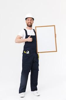 Уверенный в себе бородатый мужчина-строитель в полный рост в комбинезоне и каске, стоящий изолированно над белой стеной, показывая пустую доску