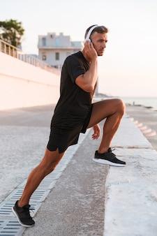Уверенный в себе спортсмен в полный рост в наушниках