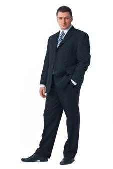 彼のポケットに片手で白に対して立っている自信を持って若いビジネスマンの全長